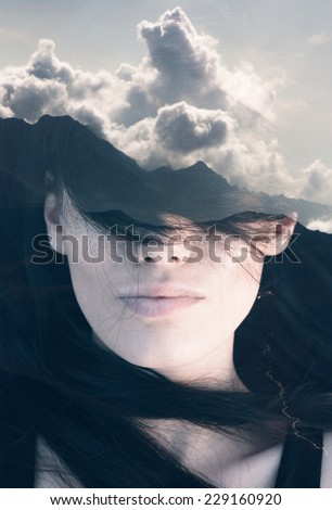 Double exposure portrait of young woman combined with photograph of mountainious landscape shot from a plane - stock photo