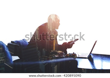 Double exposure silhouette of a skilled businessman think on the idea while is using portable net-book and touch pad.Young successful male entrepreneur is working on digital tablet and laptop computer - stock photo