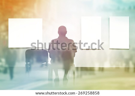 Double Exposure Silhouette of Man sitting in art gallery, looking at art displayed on walls.