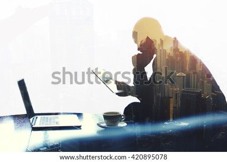 Double exposure silhouette of man skilled managing director is analyzing activities of the company by using touch pad and net-book. Thoughtful economist is reading news in network via digital tablet - stock photo