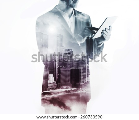 Double exposure with businessman using digital tablet - stock photo
