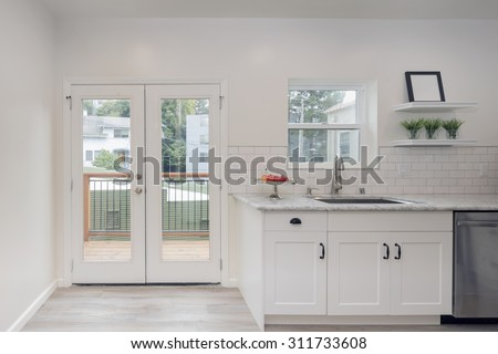 Double french doors with framed glass windows in kitchen. French doors leading to outdoors. - stock photo