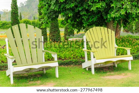 double green wood chairs stand outdoor in the garden - stock photo