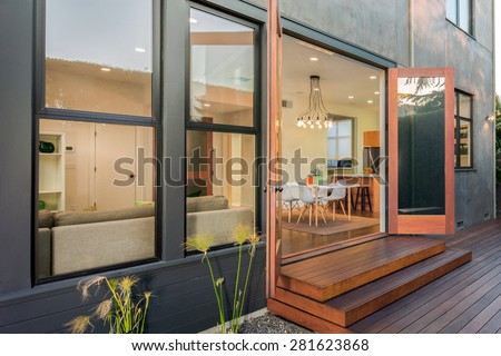 Double open french doors leading into contemporary home with wooden terrace, open floor plan, greenery at night. Large window showing modern interior at twilight.  - stock photo