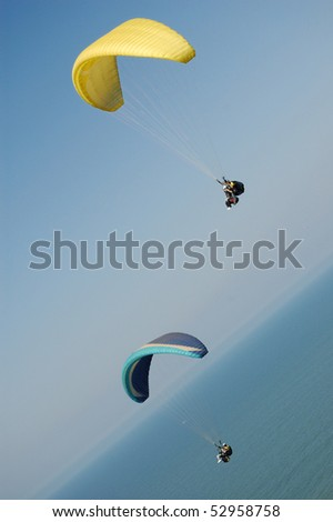 Double Paragliding flying through the sky above the ocean