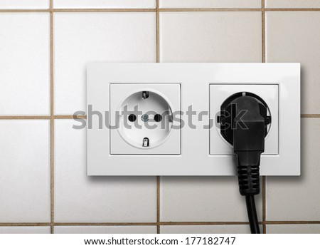 double power European electric plug on tiled wall
