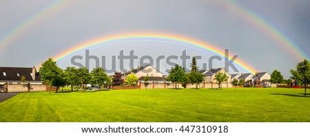 Double rainbow appears over a housing area against a dark sky in Ireland - stock photo