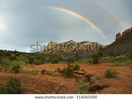 Double rainbow arching over mountains of Sedona at sunset - stock photo