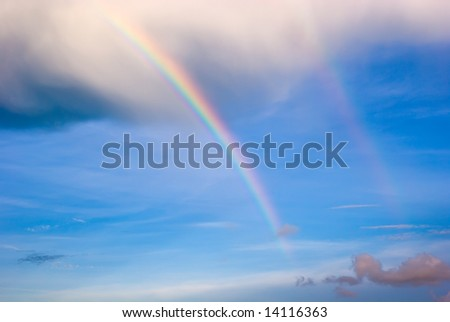 Double Rainbow Extending Below Base of Clouds in Blue Sky