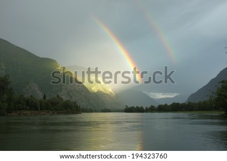 Double rainbow over the lake. Amazing play of light after the rain in the mountains, Altai. Window in a heaven. Door in the paradise. Rainbow reflection in the water. - stock photo