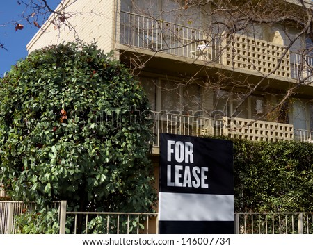 double story townhouses or apartments for lease with hedged front garden - stock photo