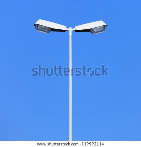 Double street light lamp post or lantern on a blue sky background - stock photo