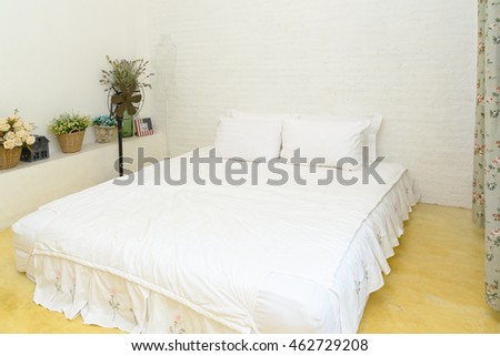 Double white bed in the bedroom.