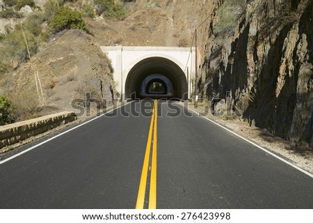 Double yellow-line leads to a tunnel through a mountain on highway 33 in Ojai, Ventura County California - stock photo