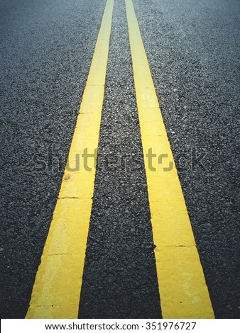 Double yellow lines on a black tarmac/asphalt road in New Jersey, USA