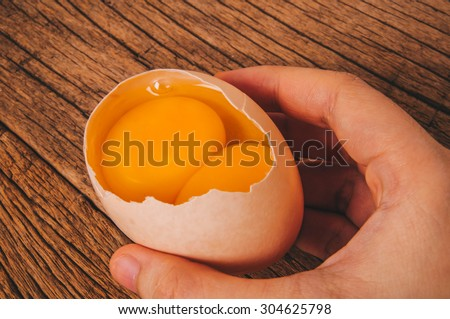 Double Yolks, Fresh Twin Egg Yolks in Egg Shell with Hand Holding on Wood Table Background, Country Rustic Style. Concept Idea of Cooking and Baking.  - stock photo