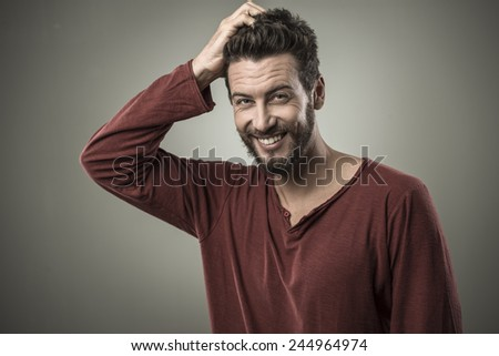 Doubtful smiling young man touching his head and thinking - stock photo