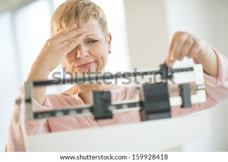 Doubtful woman adjusting weight scale - stock photo
