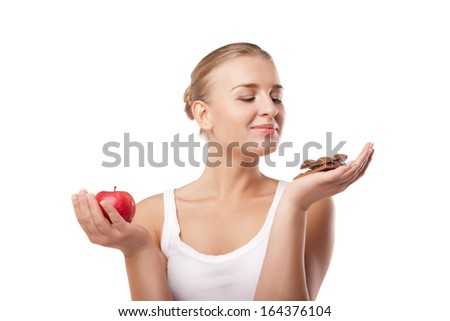 Doubtful woman holding an apple and chocolate trying to decide which one to eat on white background - stock photo