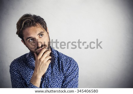 Doubtful young man looks up at copy space - stock photo