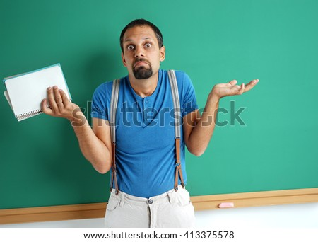 Doubting teacher spreads his hands looking at camera. Photo of adult man think through near blackboard. Education concept - stock photo