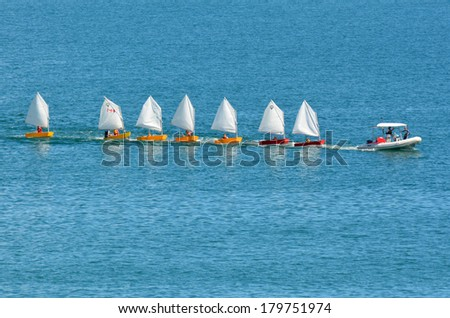DOUBTLESS BAY, NZ - FEB 15:Motor boat with sailing instructor drags a line of small sailing boats on Feb 15 2014.New Zealand is one of the top sailing nation in the world. - stock photo