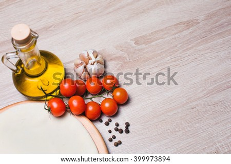 Dough basis for the pizza on a wooden board and cherry tomatoes, olive oil, spices, garlic. - stock photo