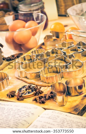 Dough cookie cutters Christmas gingerbread iced. Kitchen table with ingredients - stock photo