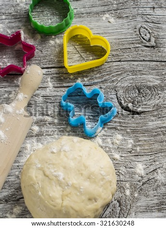 dough, cookie cutters, rolling pin on a light wooden background, cooking cookies