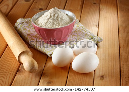 dough, eggs and roller pin on wooden background