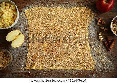 Dough for apple pie on kitchen table - stock photo