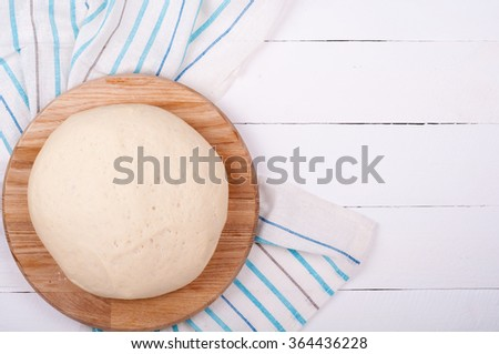 Dough for bread or pizza and kitchen towel on old rustic wooden background. Homemade baking bread. Dough background with copy space. Top view - stock photo