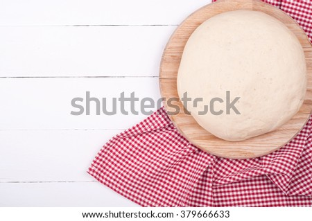 Dough for bread or pizza and kitchen towel on white rustic wooden background. Homemade baking bread. Dough background with copy space. Top view