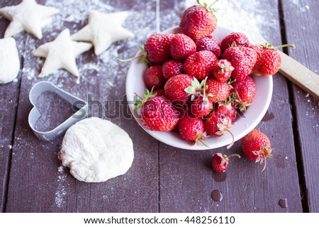 Dough for cookies, ripe strawberry and berries of a honeysuckle. Food concept on a wooden background. - stock photo