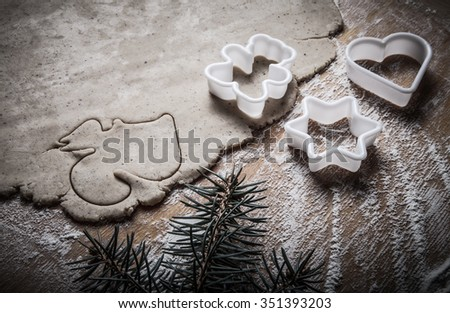 Dough for gingerbread cookie and cookie cutters in different shapes on light wooden cutting board like background. Toned.