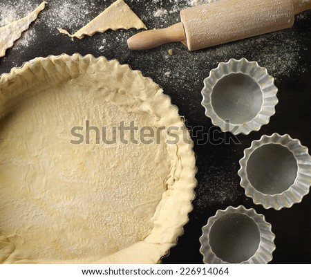 dough in a baking tart form and rolling pin - stock photo