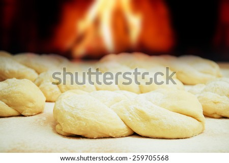 Dough in scattering flour on wooden table. - stock photo
