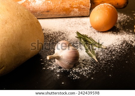 dough on a black board with flour. eggs, rolling pin, garlic. Tinted  - stock photo