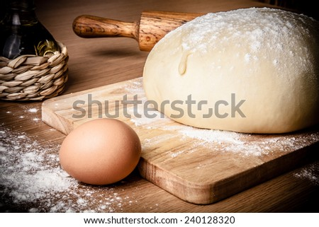 dough on a board with flour. olive oil, eggs, rolling pin - stock photo