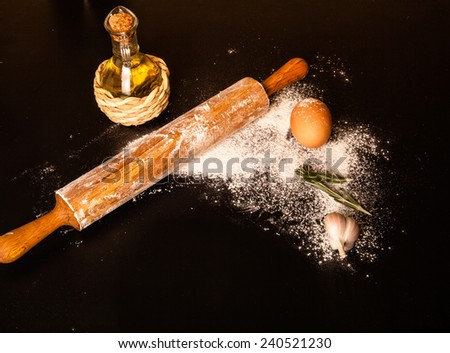 dough on a board with flour. olive oil, eggs, rolling pin, garlic  - stock photo