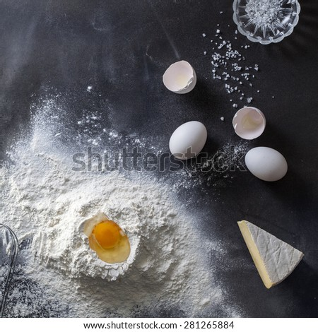Dough on black table with flour and ingredients. Top view - stock photo