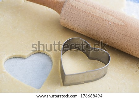 Dough rolled out with heart shape cut out, and heart shaped cookie cutter - stock photo