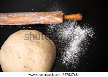 Dough, rolling pin and flour on a black background. - stock photo