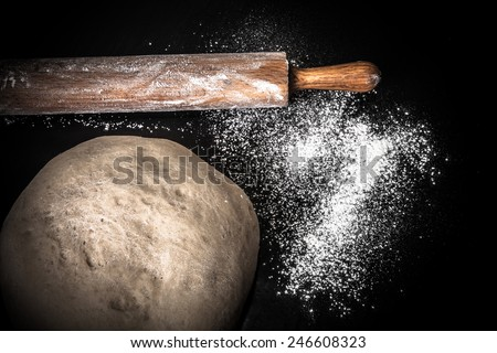 Dough, rolling pin and flour on a black background. Toned.