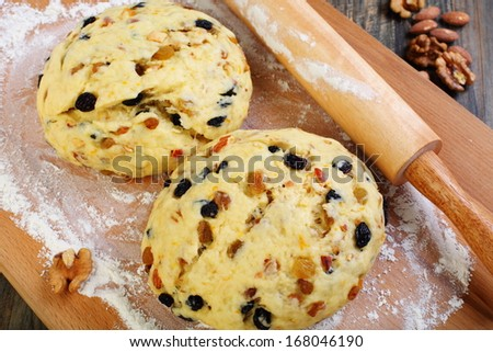 Dough with candied fruits and nuts for Christmas baking on a cutting board.