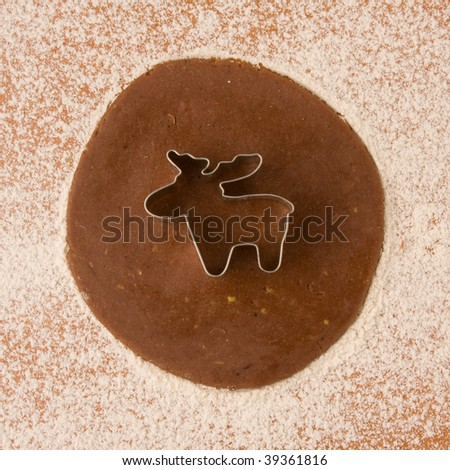 dough with cookie cutter reindeer shape - stock photo