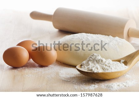 Dough with eggs  on wooden table. Selective focus