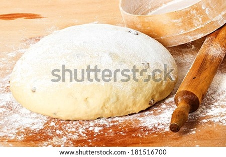 dough with rolling pin on floured table top view - stock photo