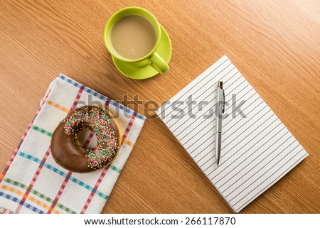 doughnut coffee and notepad with pen on a table - stock photo