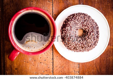 Doughnut. Sweet food and red cup of coffee, tea drink. Breakfast, dessert with cake, snack. Brown wooden table. Bakery, sugar doughnut. Tasty espresso black hot morning beverage.  - stock photo